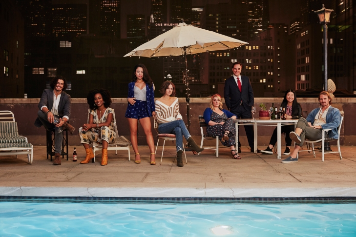 The cast of Good Trouble stand and sit on patio furniture by a pool in a promo shot