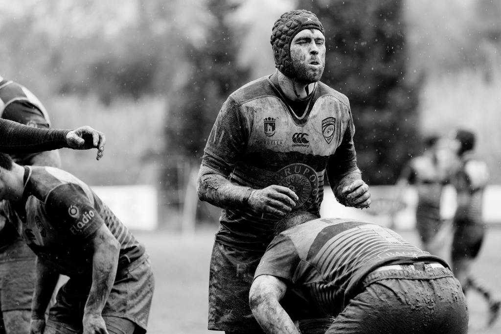 A black and white photo showing one male rugby player standing while another player bends in front of him, his head at crotch height. Both are covered in mud.