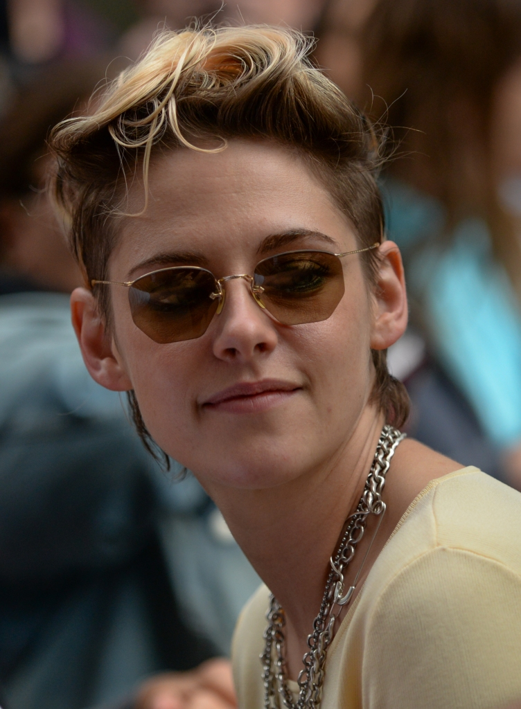 Kristen Stewart, smiling slightly, with short messy blonde hair, cool sunglasses and thick silver chains around her neck.