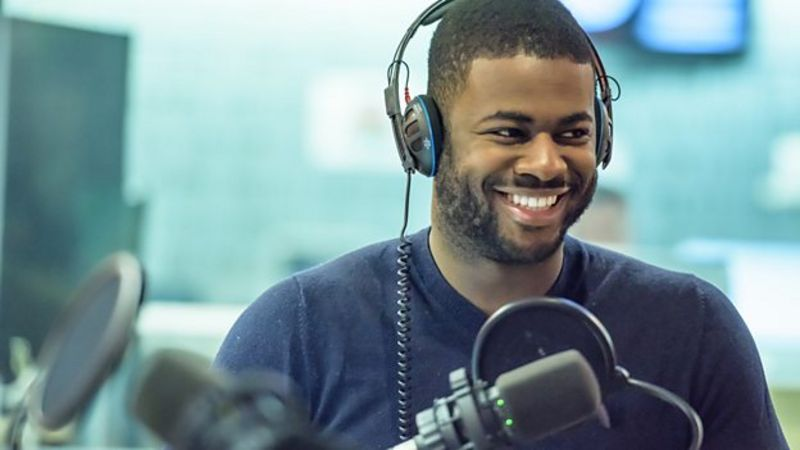 Ben Hunte wears headphones in a radio studio and smiles to someone off camera.