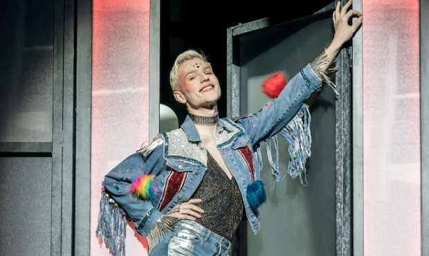 John McCrea as Jamie stands in a doorway in a fringed denim jacket with diamante decoration. He has a huge smile on his face.