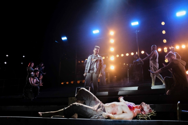 A scene from Jesus Christ Superstar. Jesus, bloodied, lies on the floor as Judas looks down at him.