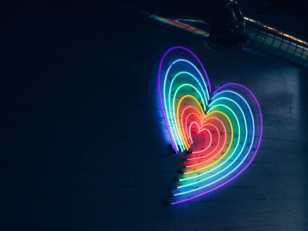 A neon rainbow coloured heart sign glows against a dark wall.