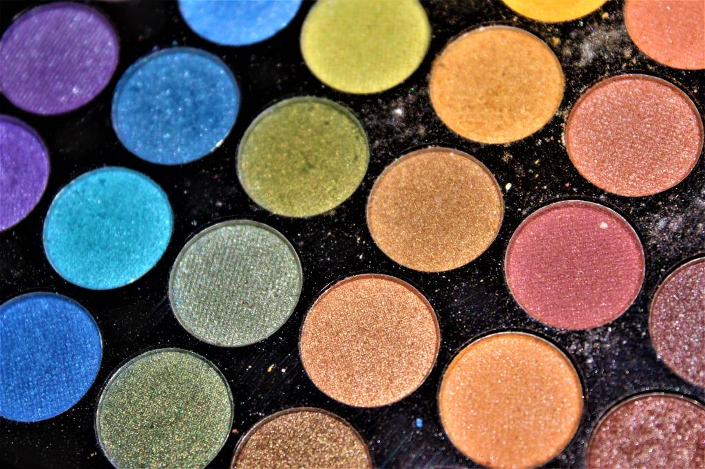 A close-up of a palette of rainbow-coloured sparkly eyeshadows.