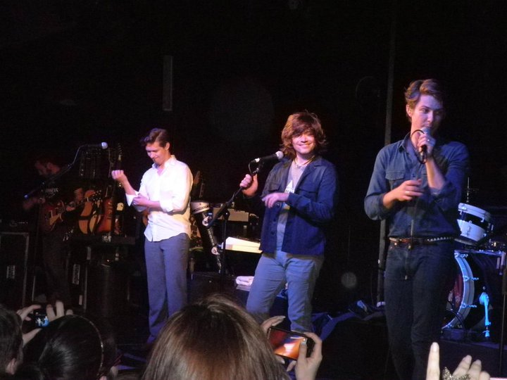 Hanson standing behind microphones onstage