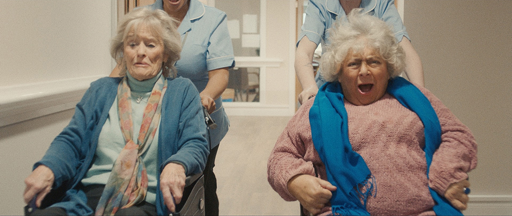 Virginia McKenna and Miriam Margolyes sit in wheelchairs side by side, smiling as they're pushed at high speed down a corridor by nurses in blue uniforms