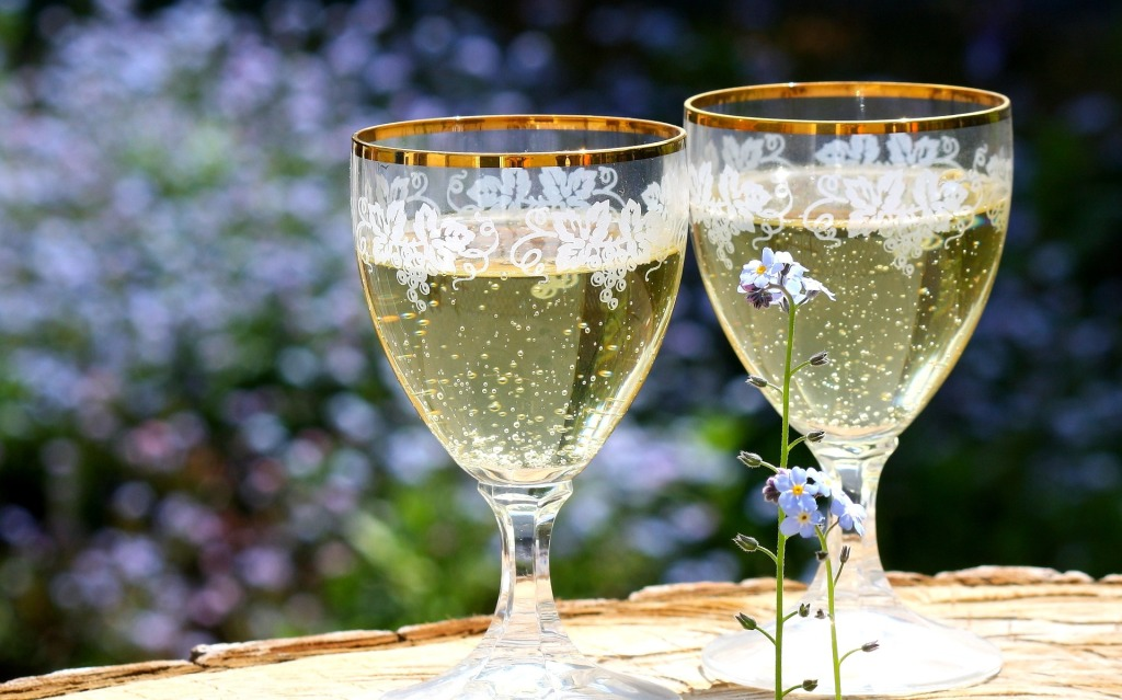 Two rounded champagne glasses with gold rims and delicate floral etching, with a stem of small blue flowers in the foreground
