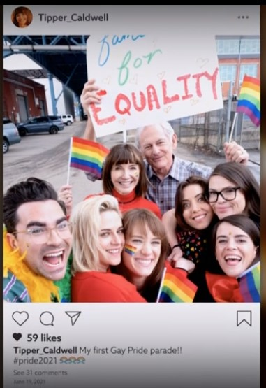 A screenshot of a mockup instagram post from the Happiest Season credits, showing the entire main cast waving rainbow flags plus director Clea DuVall, who has her arm around Aubrey Plaza.