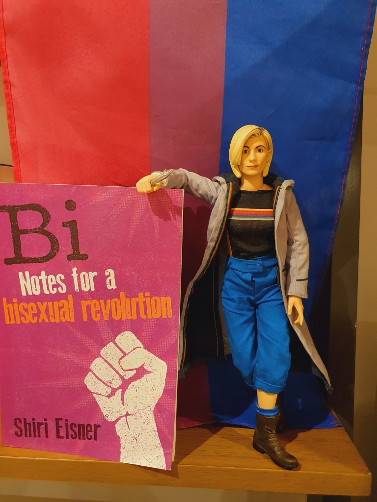 An action figure of Jodie Whittaker as Doctor Who stands on a wooden shelf, leaning on a copy of Bi - Notes on a Bisexual Revolution by Shiri Eisner, with a bisexual pride flag as a background.