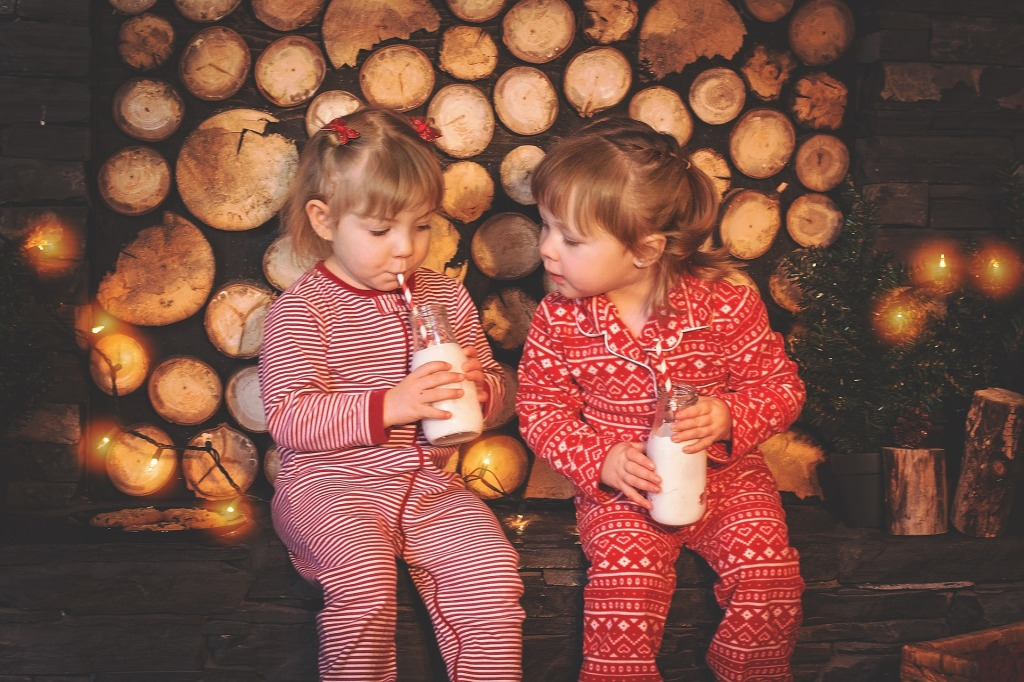 Two little white girls in red and white onesie pyjamas sit against a background of sawn-off logs and Christmas lights, drinking milk from bottles using red and white straws.