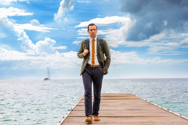 Neville Parker (Ralf Little) looks perplexed as he walks along a jetty towards the camera, with a big blue sky behind him.