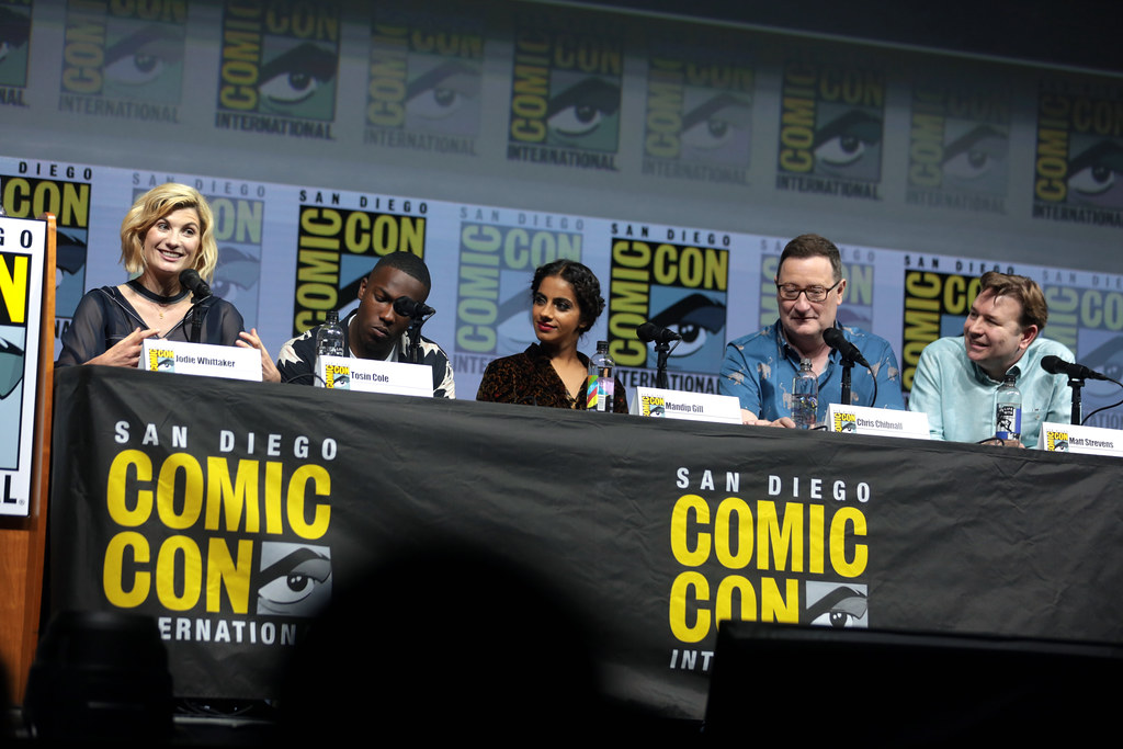 The main cast of Doctor Who and two showrunners giving a talk at San Diego Comic Con 2018. Jodie Whittaker is gesturing and Mandip Gill is listening attentively and smiling.