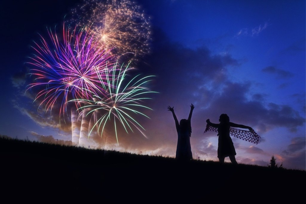 Two girls are silhouetted in front of a fireworks display at sunset. One is reaching toward the sky and one is dancing with a sheer scarf, arms outstretched.