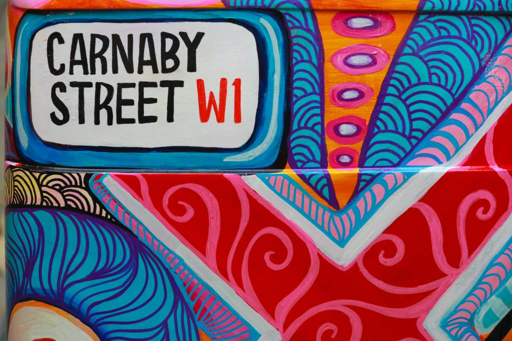 """A wall painted in colourful stripes, swirls and patterns, with a block at the top left reading """"Carnaby Street W1"""""""