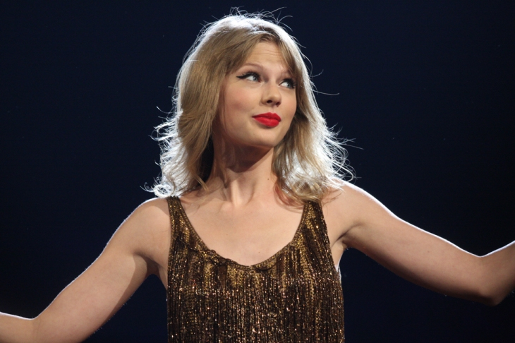 Taylor Swift is dressed in a golden sequinned dress and loose hair, with bright red lips, shrugs.